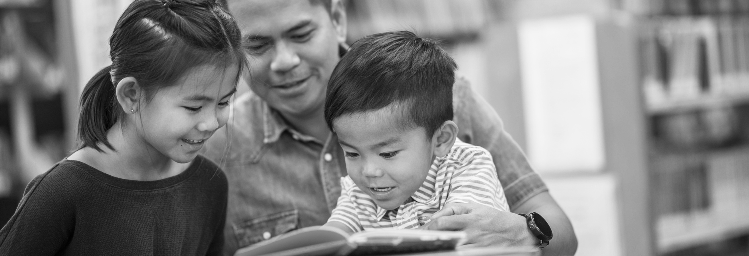 dad reading book with his young daughter and son